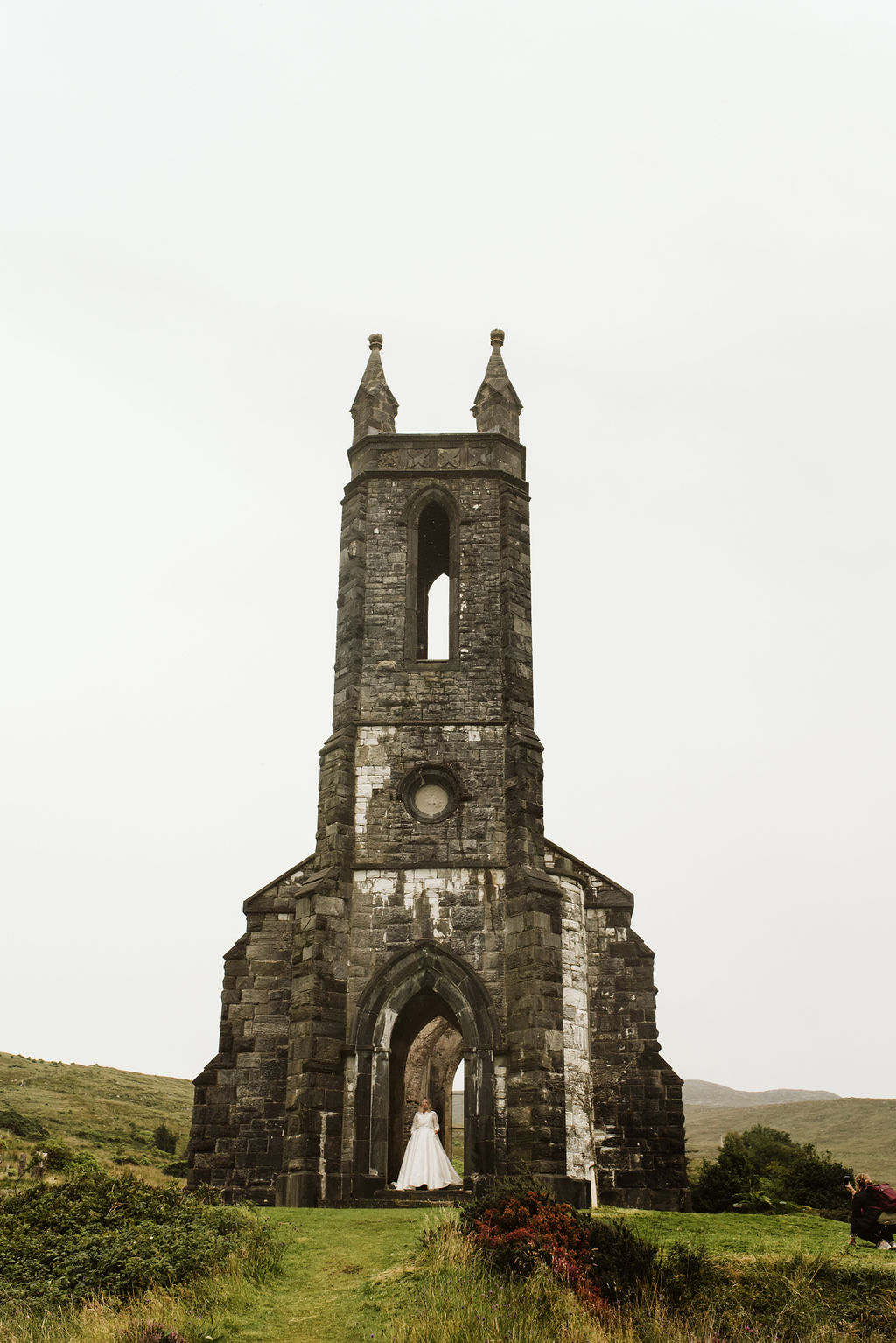 Pulled back view of bride in doorway of abandoned church wearing a mikado ballgown wedding dress and lace bomber jacket at Dunlewey Church in Ireland