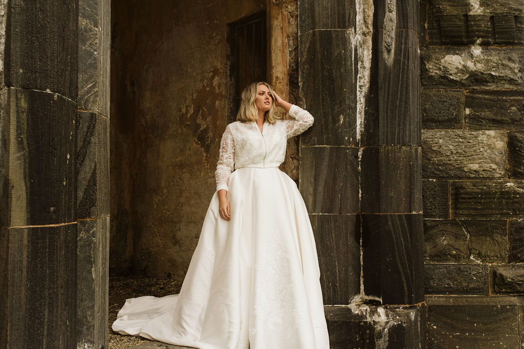Bride standing in doorway of abandoned church wearing a mikado ballgown wedding dress and lace bomber jacket at Dunlewey Church in Ireland