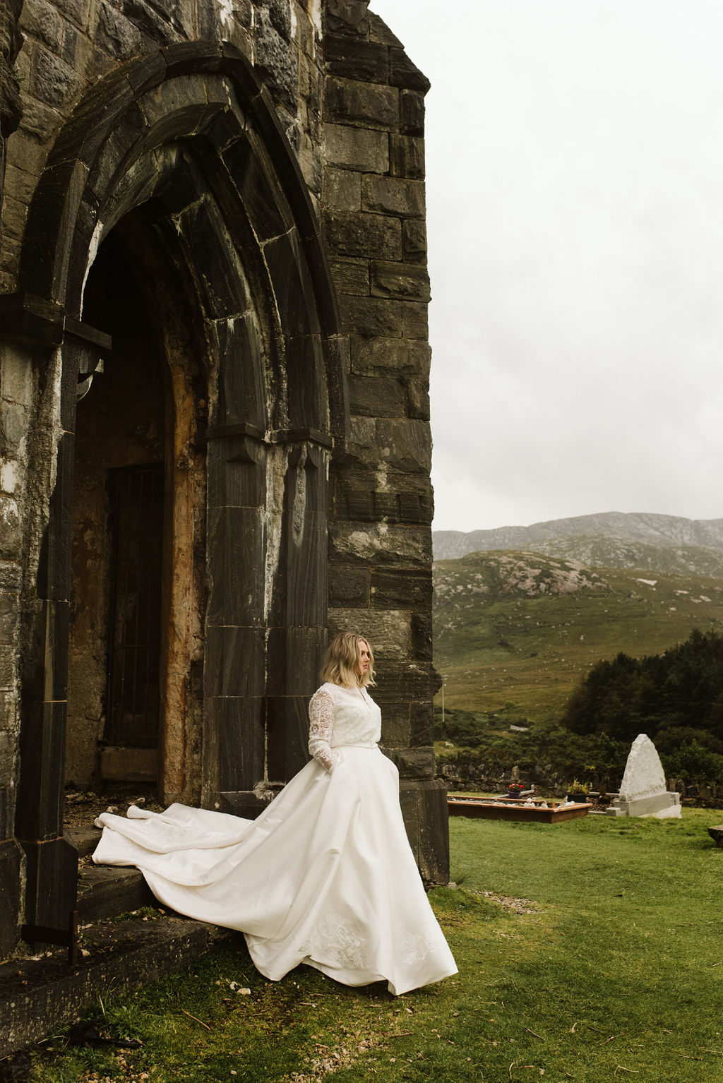 Bride walking out of the doorway of abandoned church with her hands in the pockets of her mikado ballgown wedding dress and lace bomber jacket at Dunlewey Church in Ireland