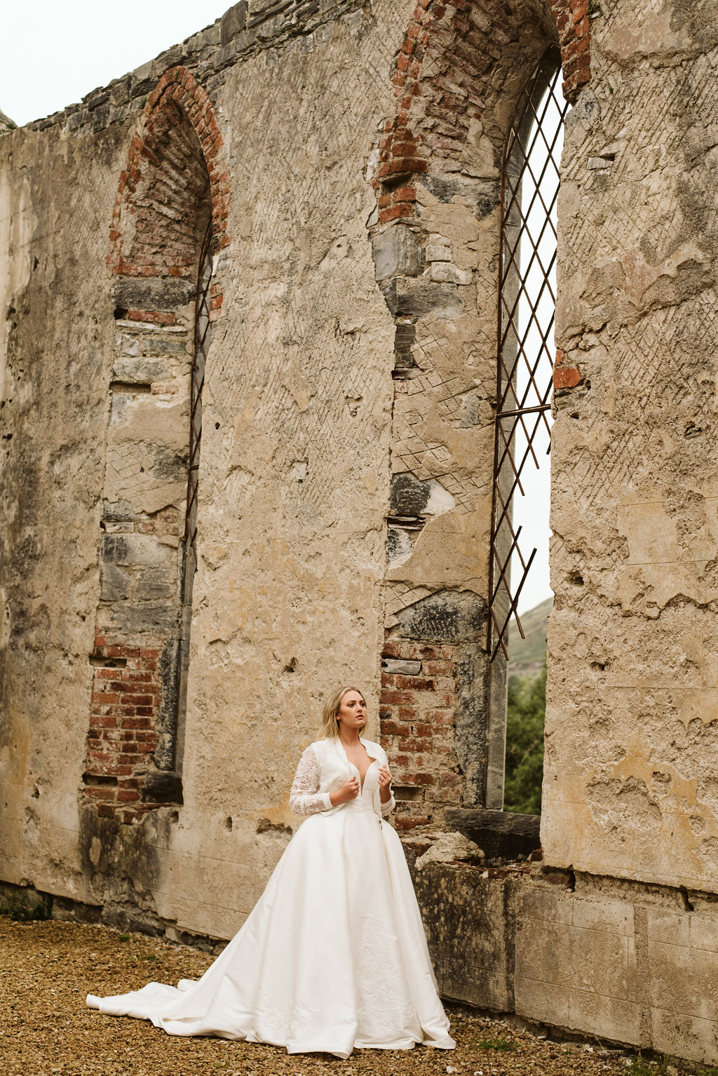 Bride walking through Dunlewey Church in Ireland wearing a mikado ballgown wedding dress and lace bomber jacket