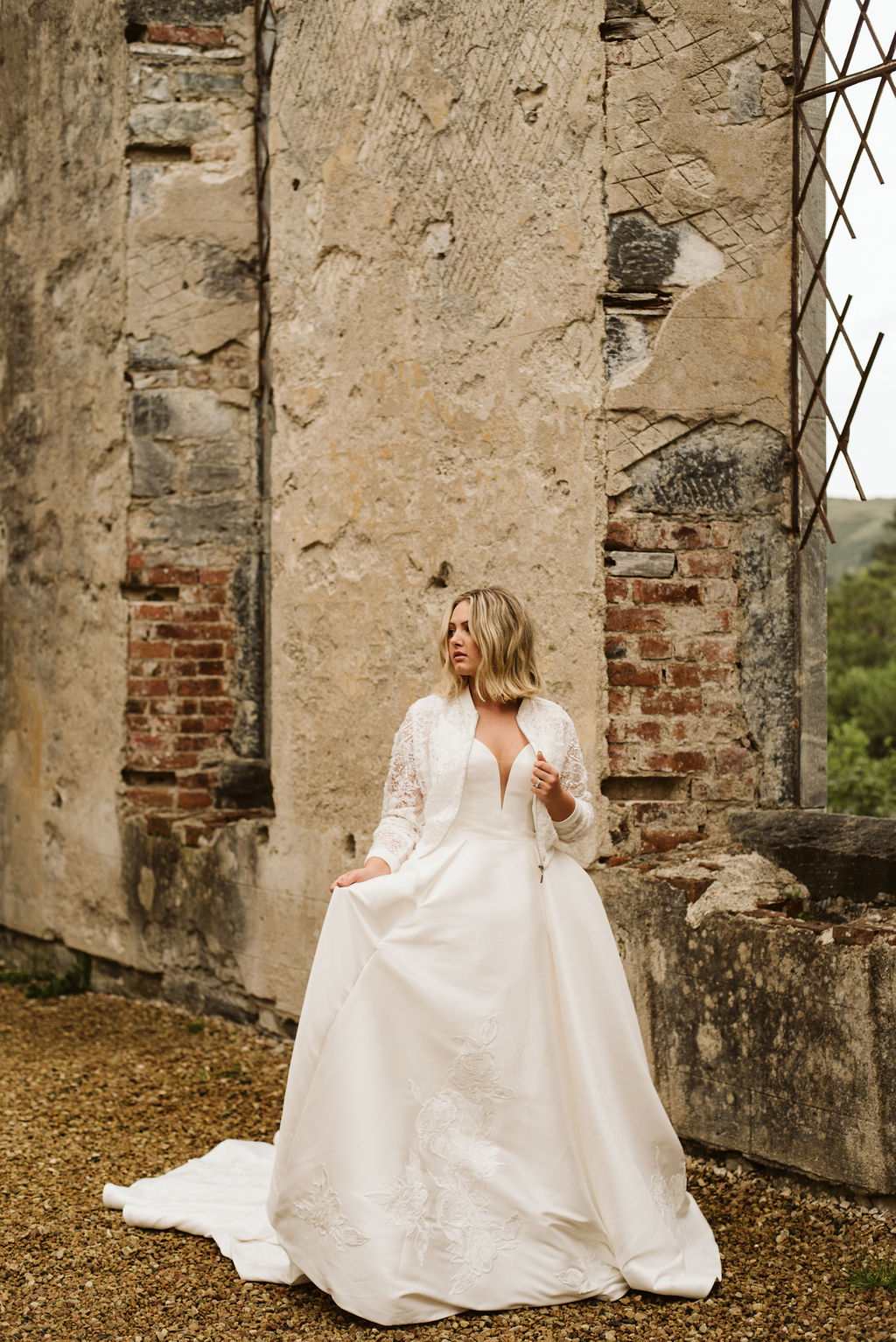 Bride walking through abandoned church wearing a mikado ballgown wedding dress with lace detail at the bottom of the skirt and a lace bomber jacket at Dunlewey Church in Ireland
