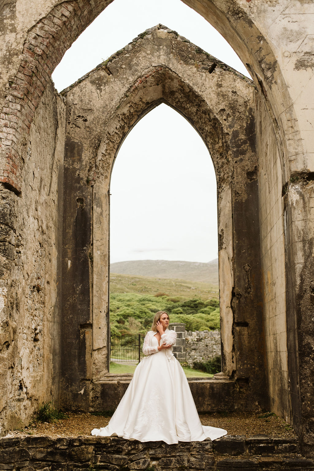 Bride standing in the abandoned altar area of Dunlewey Church wearing a mikado ballgown wedding dress and lace bomber jacket in Ireland