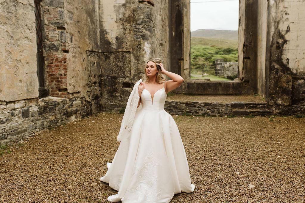 Bride has her lace bomber jacket slung over her shoulder wearing a mikado ballgown wedding dress at Dunlewey Church in Ireland