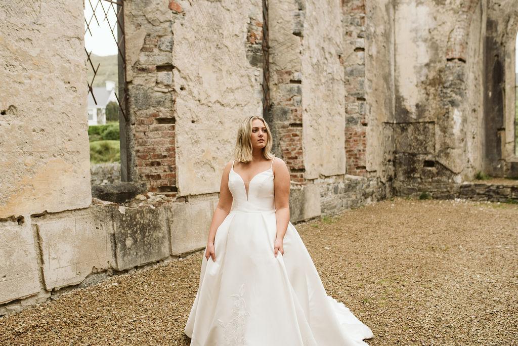 Bride walking through the abandoned Dunlewey Church in Ireland wearing a mikado ballgown wedding dress with straps