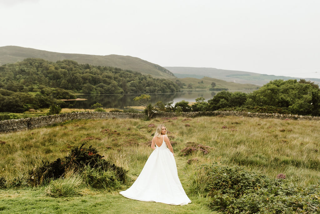 Back view of bride wearing a mikado ballgown wedding dress with straps in a field of grasses and purple flowers next to a lake at Dunlewey Church in Ireland