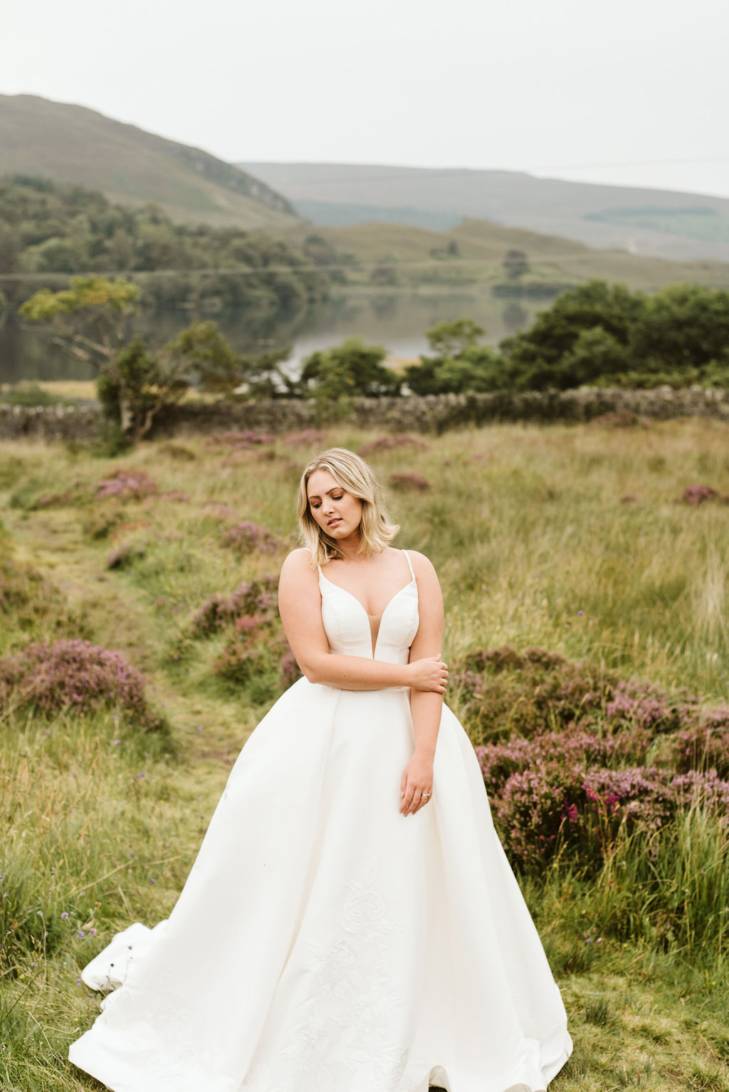 Bride standing in a field next to a lake surrounded by grasses and purple flowers wearing a mikado ballgown wedding dress with straps