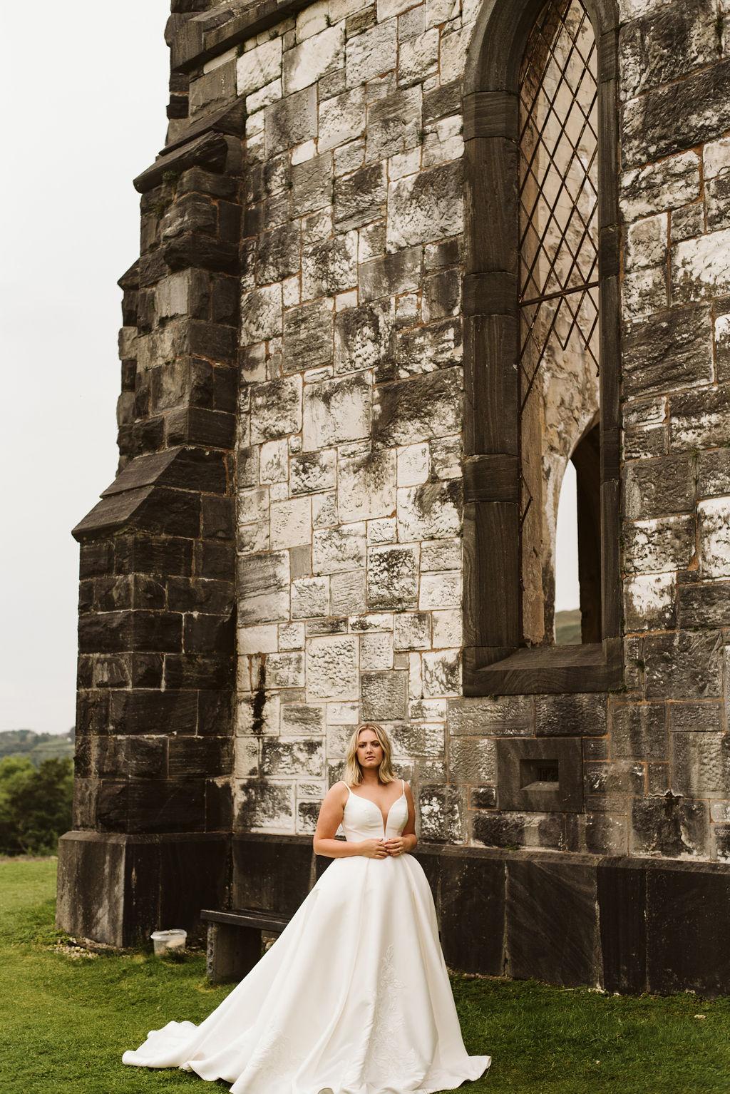 Bride walking alongside abandoned church wearing a mikado ballgown with straps at Dunlewey Church in Ireland