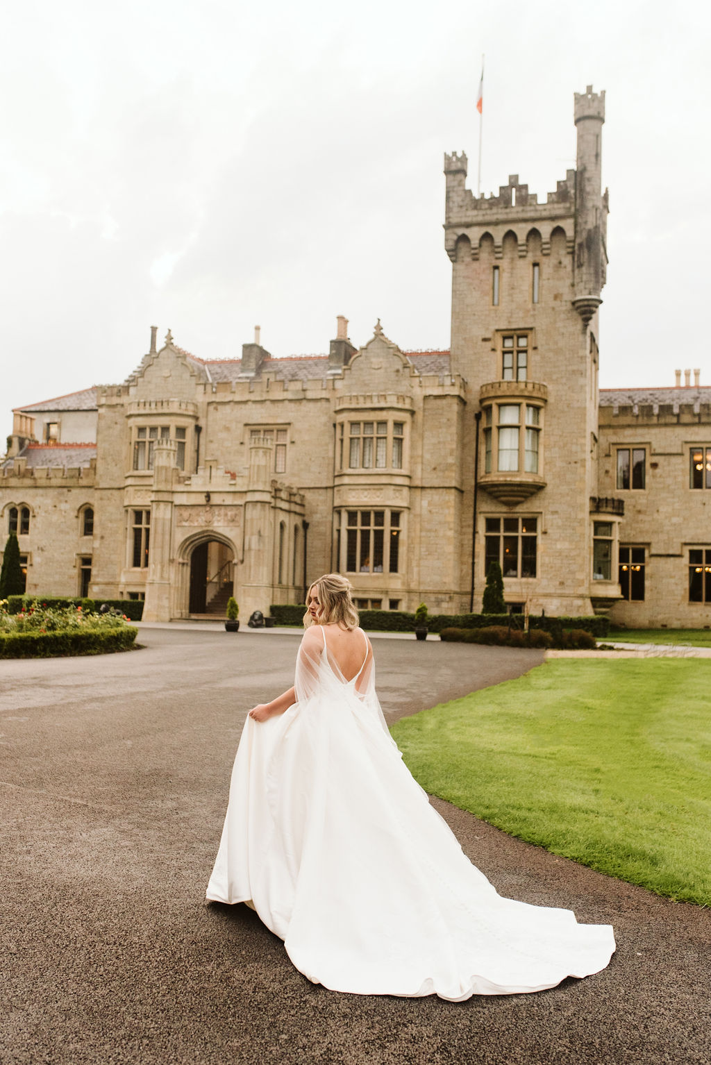 Bride wearing a mikado ballgown wedding dress with straps and a tulle cape in front of Lough Eske castle in Donegal, Ireland.