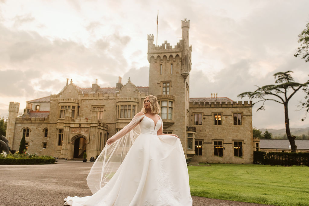 Bride wearing a mikado ballgown wedding dress with straps and tulle cape in front of Lough Eske castle in Donegal, Ireland.