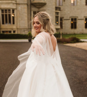 Bride reaching hand back in a mikado ballgown wedding dress and tulle cape at Lough Eske Castle in Ireland