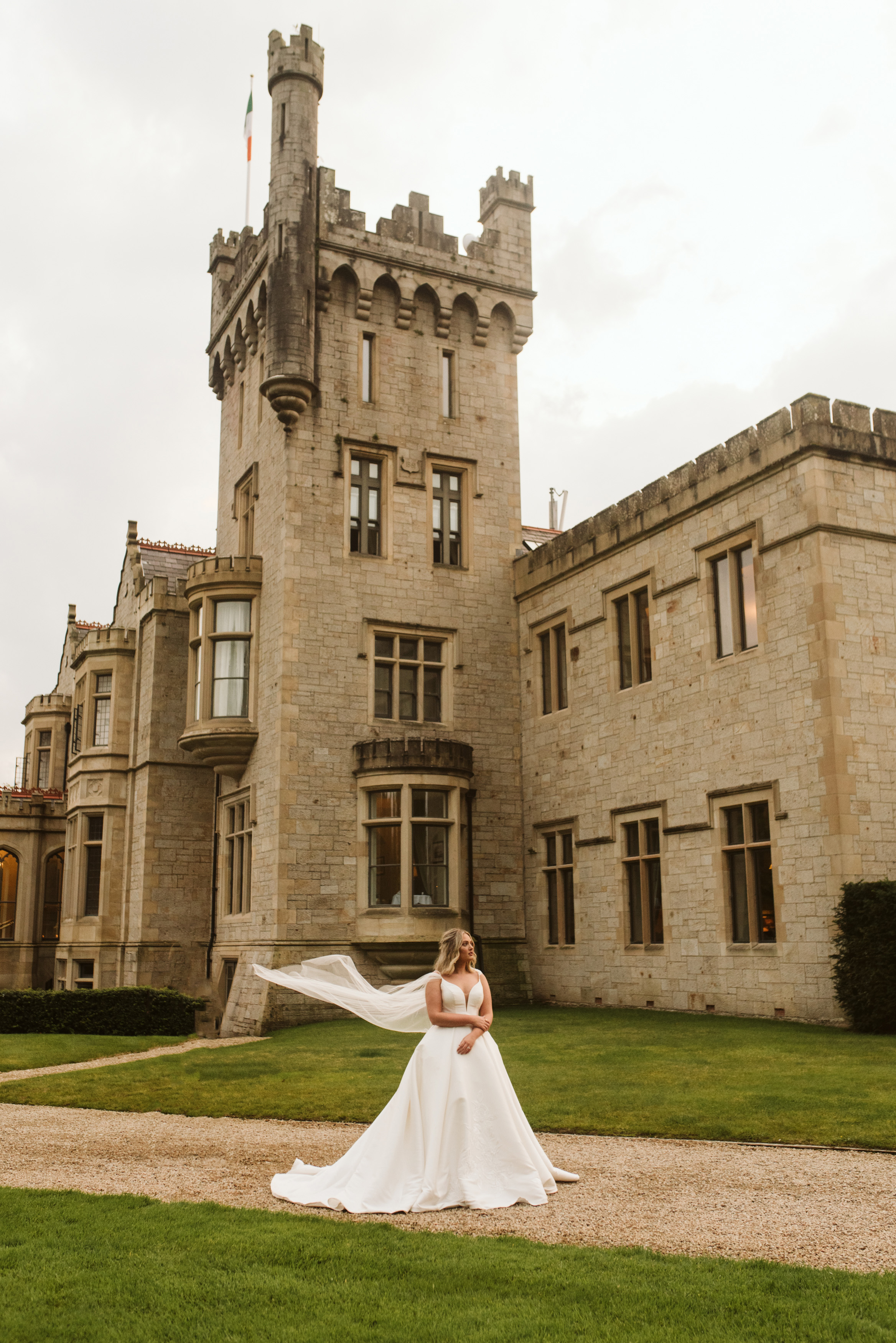 Bride in a mikado ballgown wedding dress with a tulle cape blowing in the wind at Lough Eske Castle in Ireland