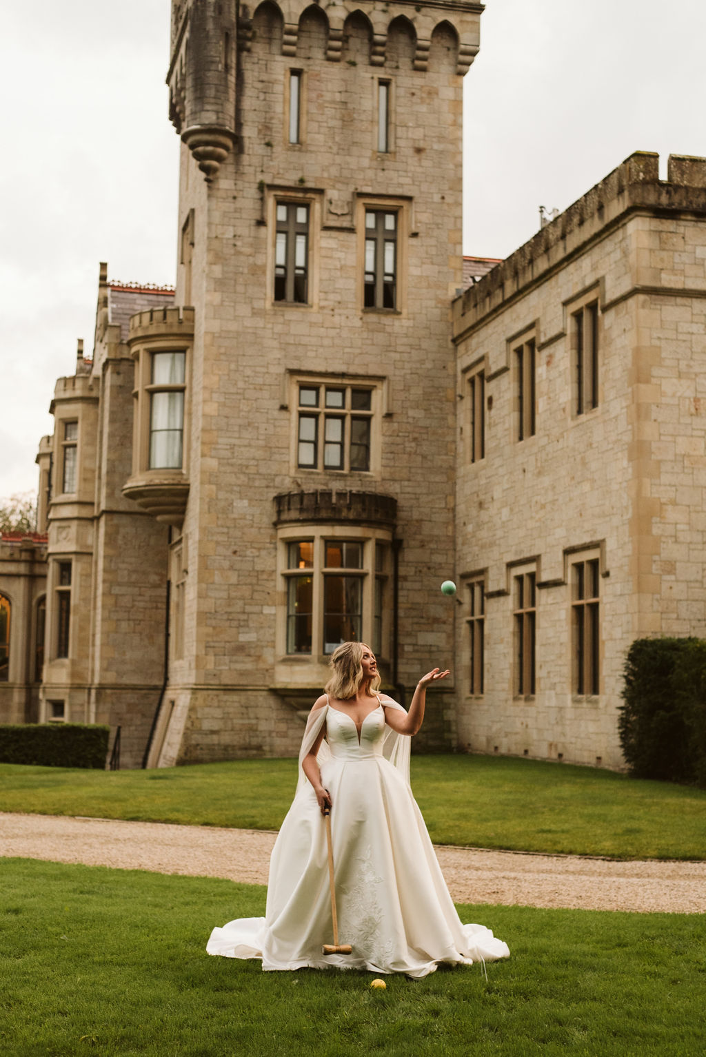 Bride wearing a mikado ballgown wedding dress with straps and tulle cape playing croquet in front of Lough Eske castle in Donegal, Ireland.