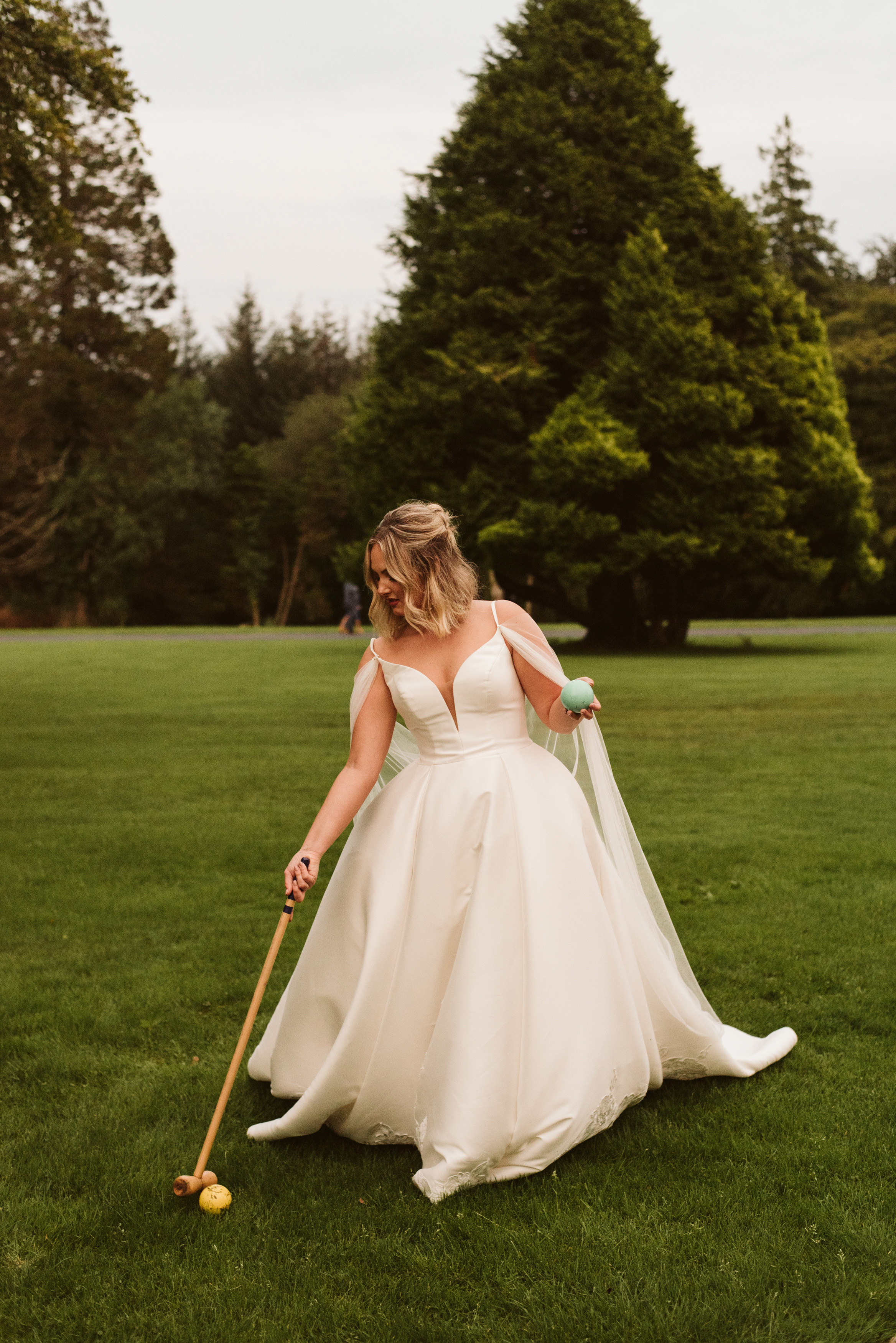 Bride playing croquet in a mikado ballgown wedding dress with straps and a tulle cape on the grounds of Lough Eske Castle in Ireland