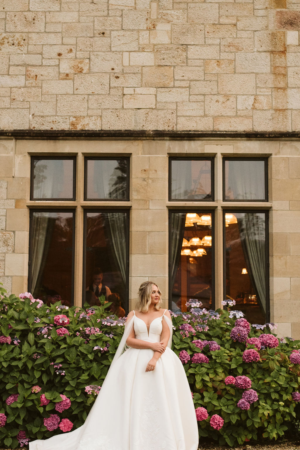 Bride wearing a mikado ballgown wedding dress with straps and tulle cape in front of hydrangeas at Lough Eske castle in Donegal, Ireland.