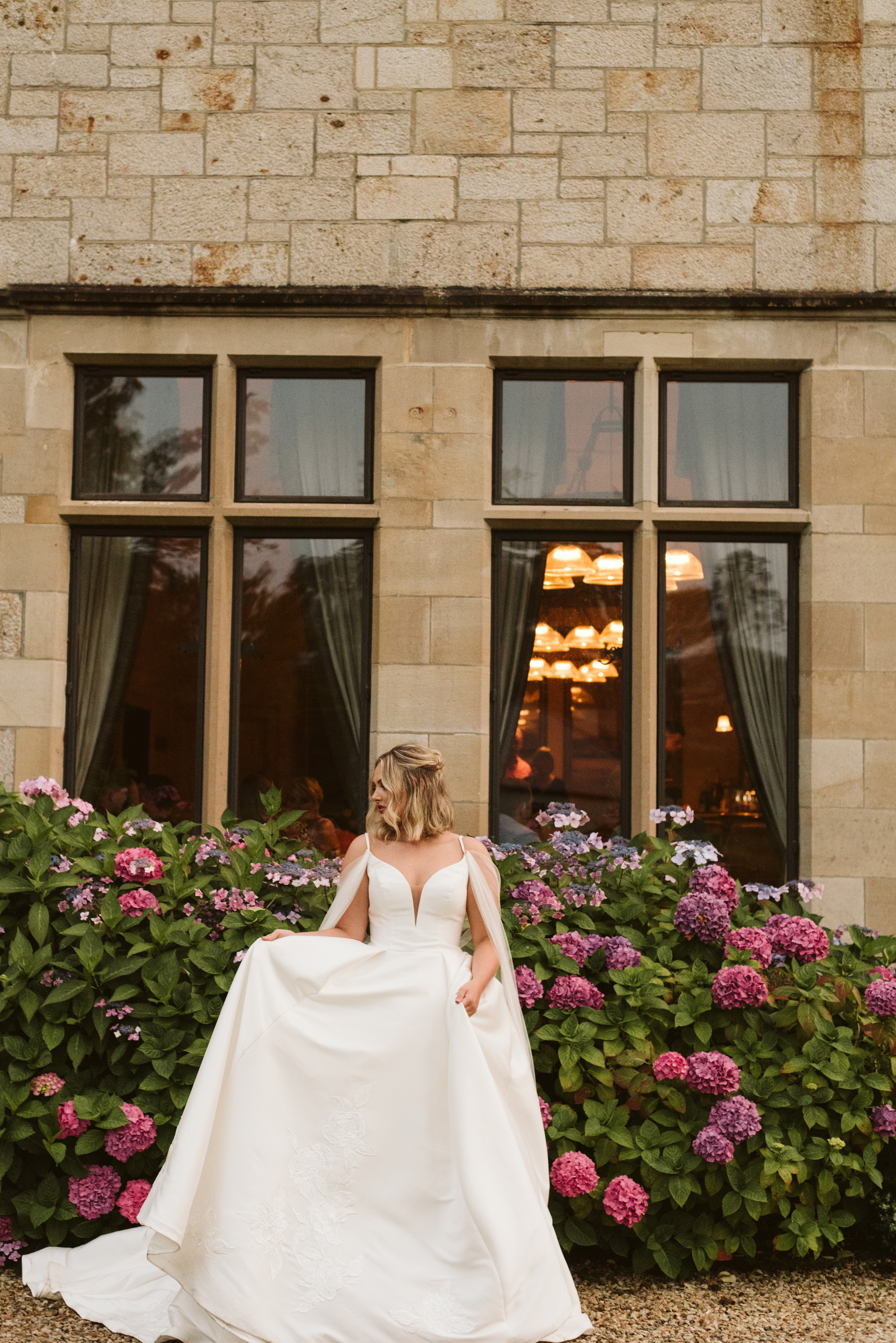 Bride in a mikado ballgown wedding dress with straps and a tulle cape standing in front of hydrangeas at Lough Eske Castle in Ireland
