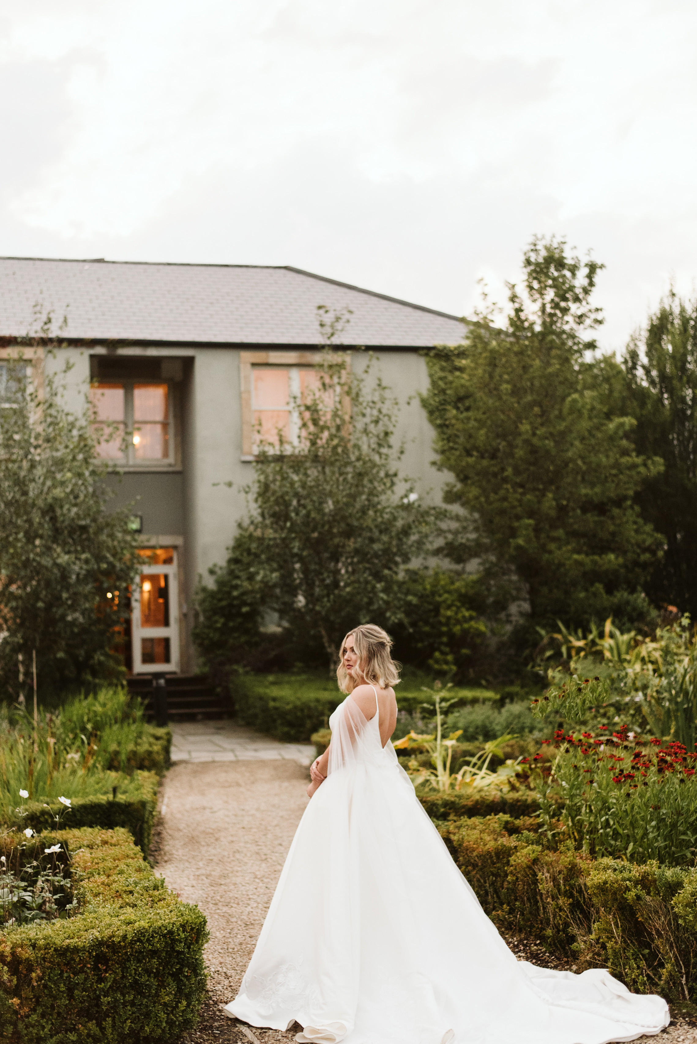 Bride walking through Gardens of Lough Eske Castle in Ireland in a mikado ballgown wedding dress and tulle cape