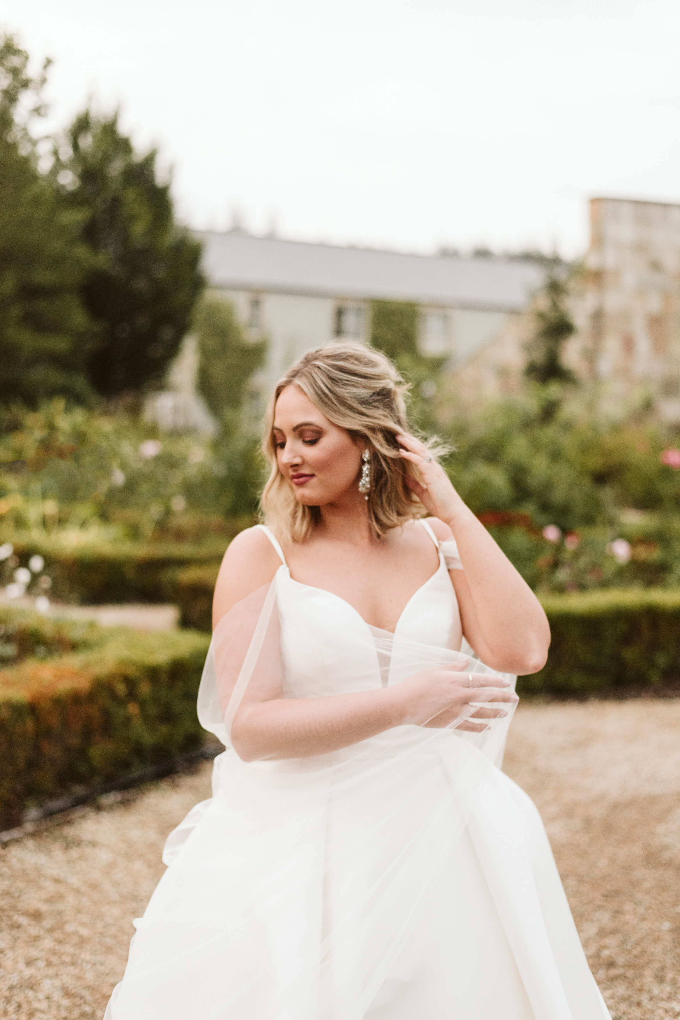 Brideshowing off her sparkly earrings in a mikado ballgown wedding dress and tulle cape at Lough Eske Castle's grounds in Ireland