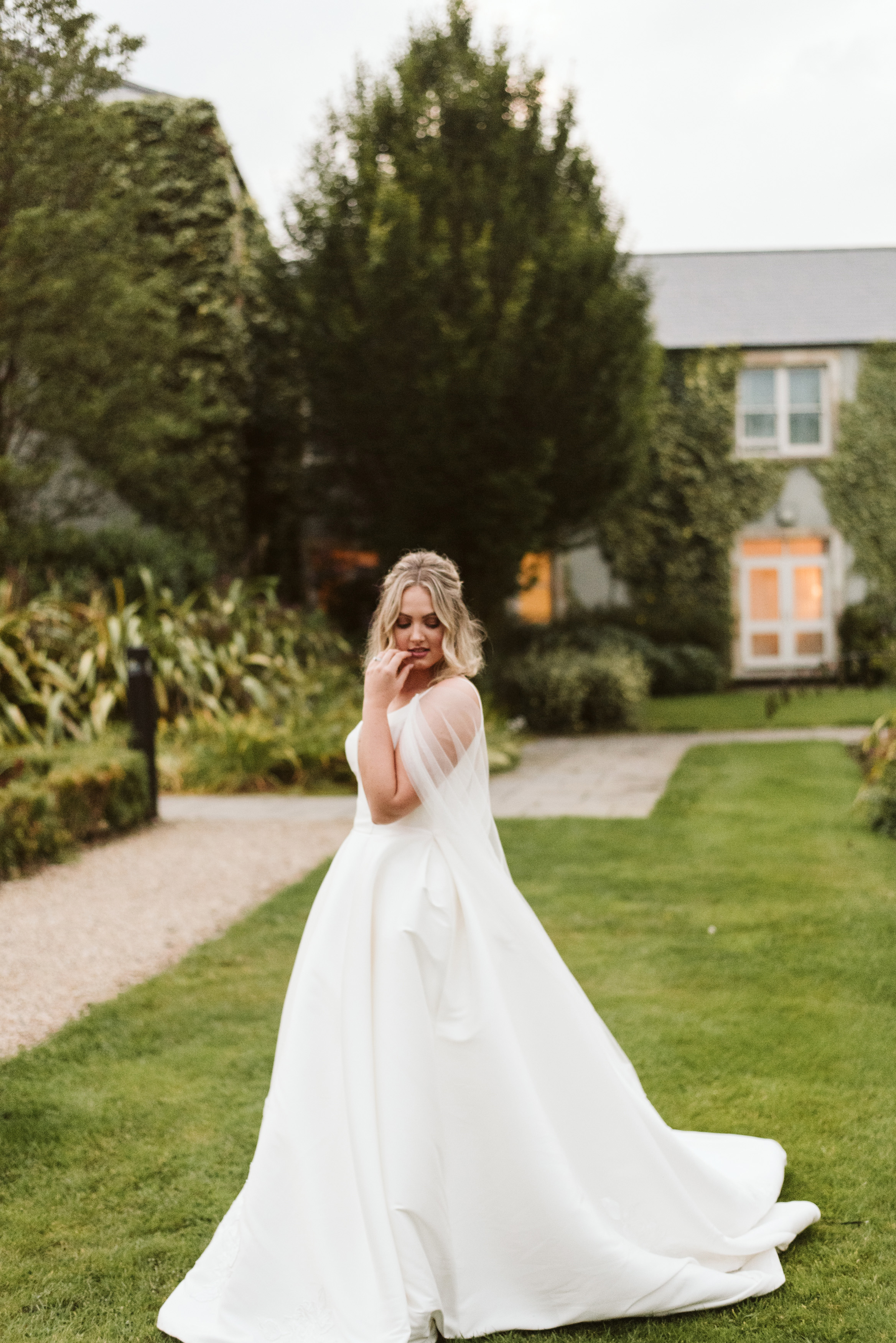 Bride in a mikado ballgown wedding dress with straps and a tulle cape walks through the garden at Lough Eske Castle in Ireland