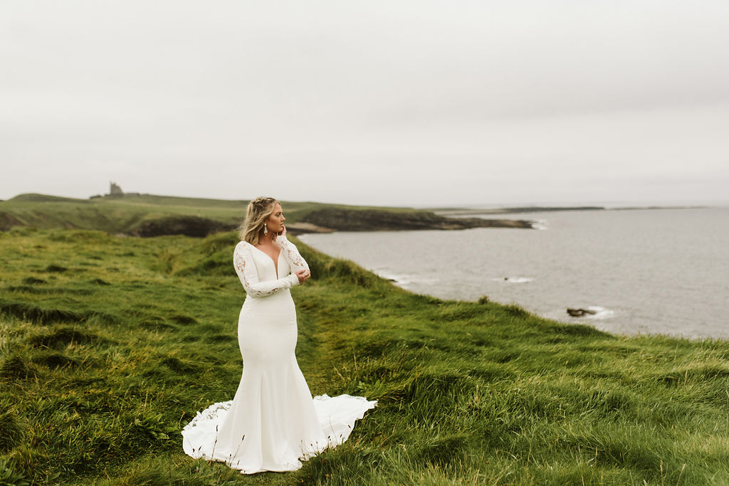 Bride looking toward Atlantic ocean wearing a fitted long sleeve crepe and lace dress with braids in her hair at Mullaghmore Head in Ireland