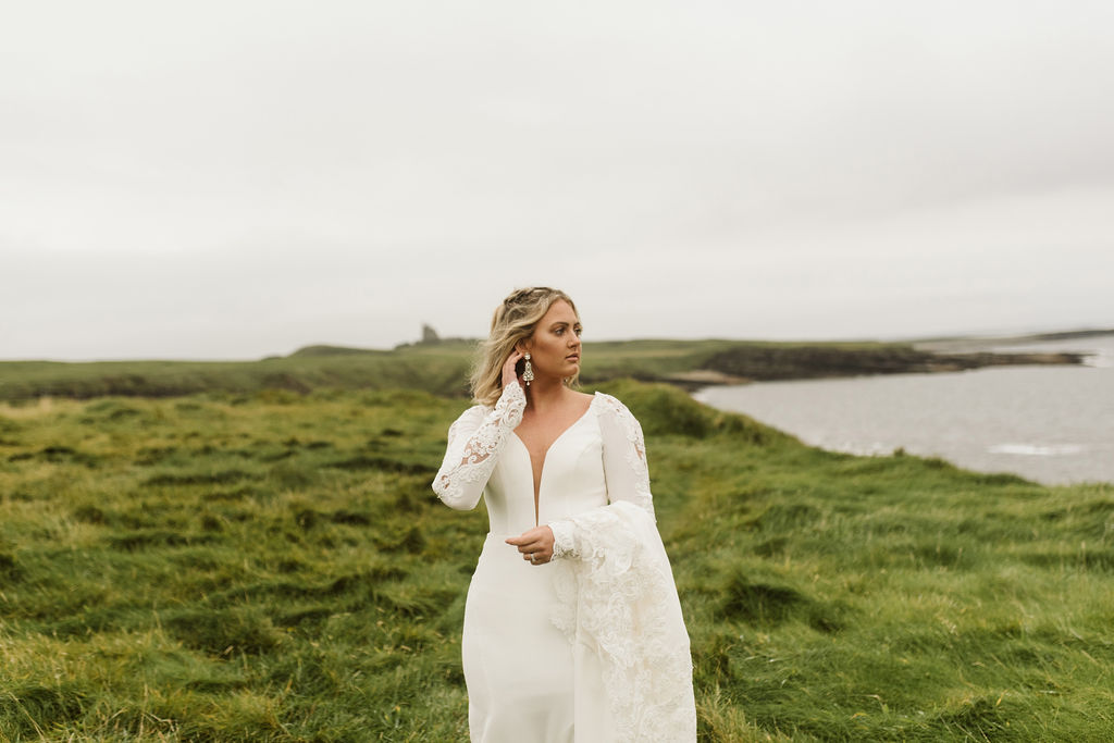 Bride carries the train of her simple fitted wedding dress with plunge neckline and long sleeves at Mullaghmore Head in Ireland