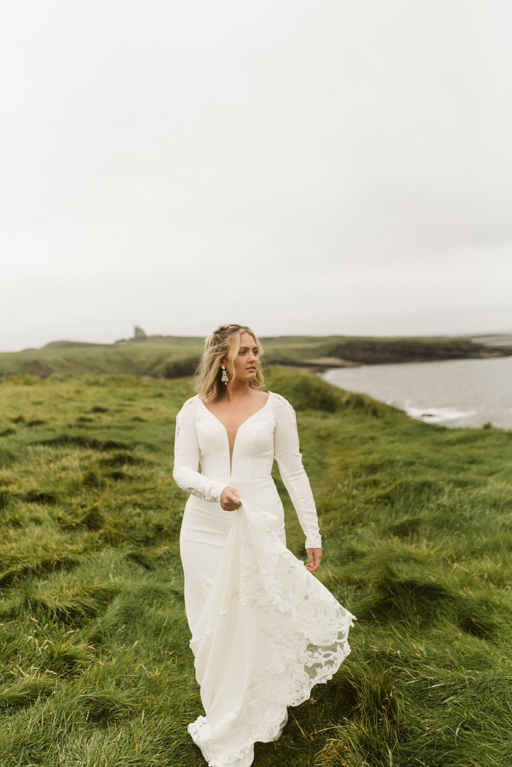 Bride swings the train of her simple fitted wedding dress with plunge neckline and long sleeves at Mullaghmore Head in Ireland