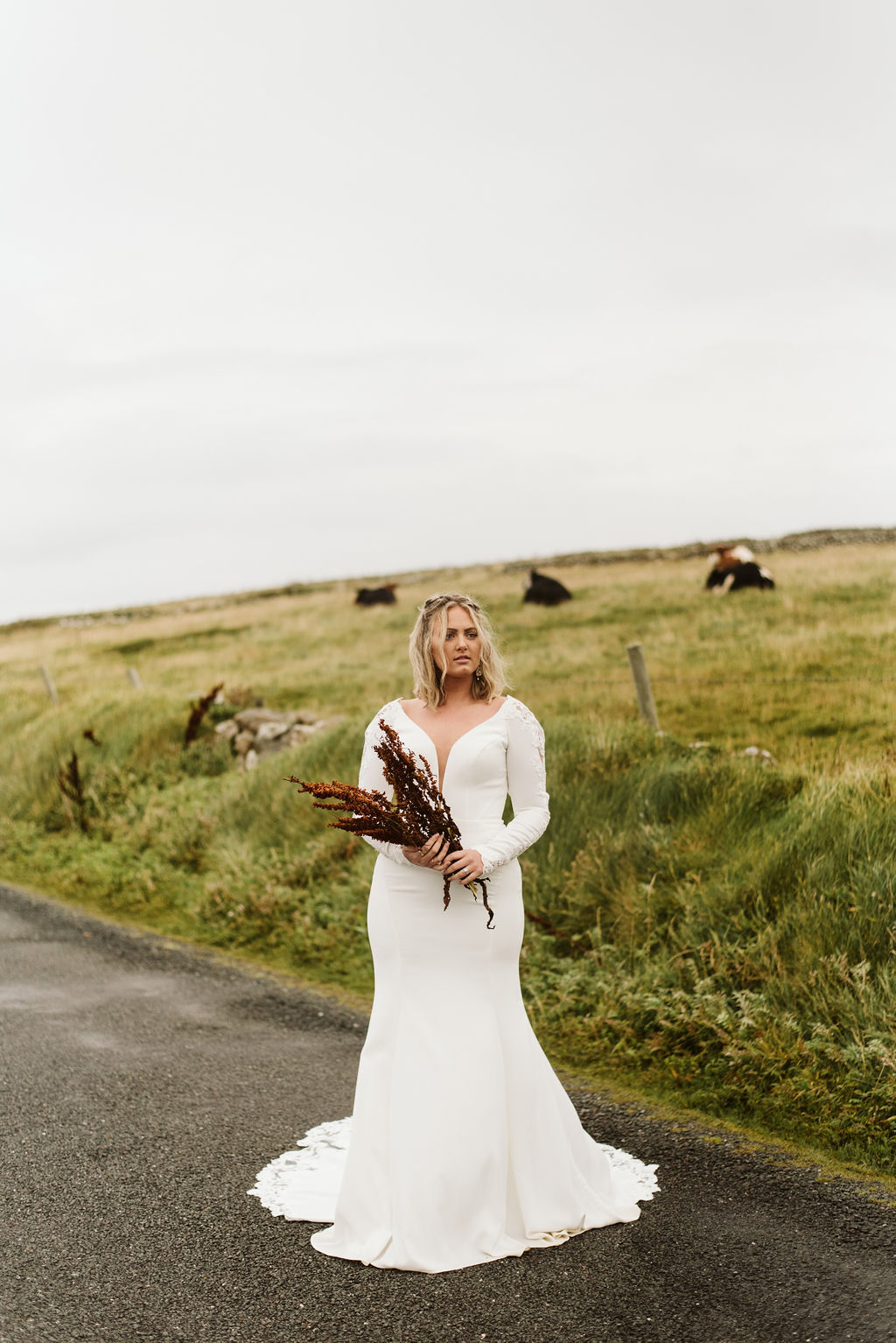 Bride holding wildflowers wearing a fitted long sleeve wedding dress at Mullaghmore Head in Ireland