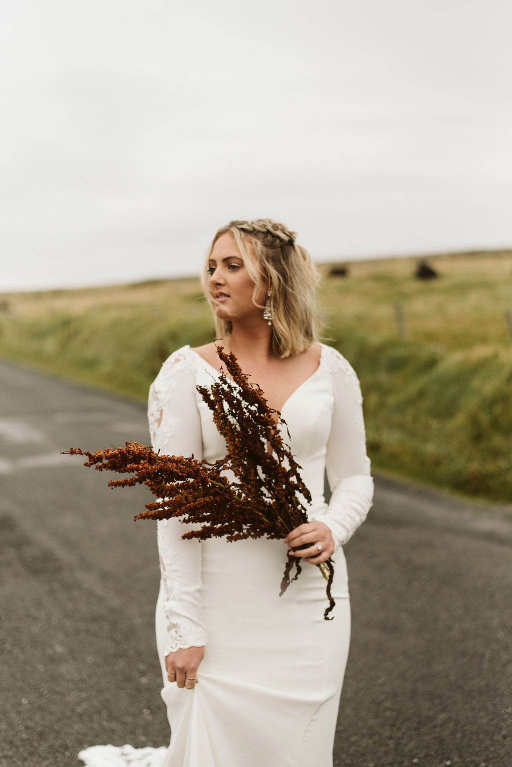 Bride with wildflowers in her hand wears a simple crepe fitted wedding dress with long sleeves and dutch braids at Mullaghmore Head in Ireland