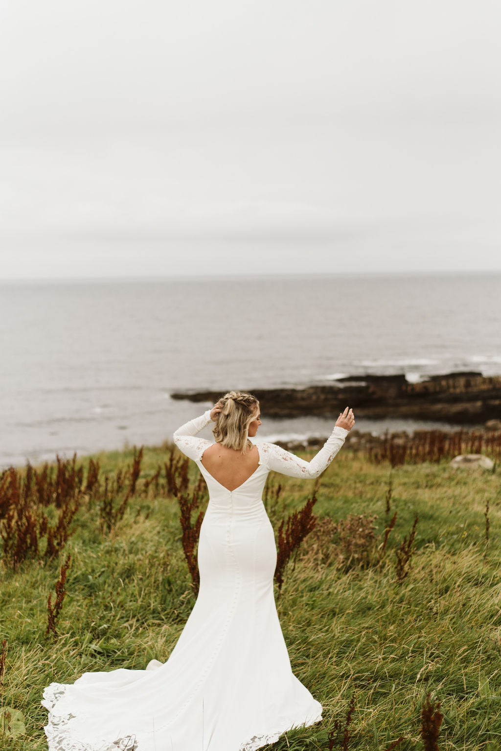 Back view of bride standing in front of Atlantic Ocean wearing a long sleeve crepe and lace wedding dress at Mullaghmore Head in Ireland