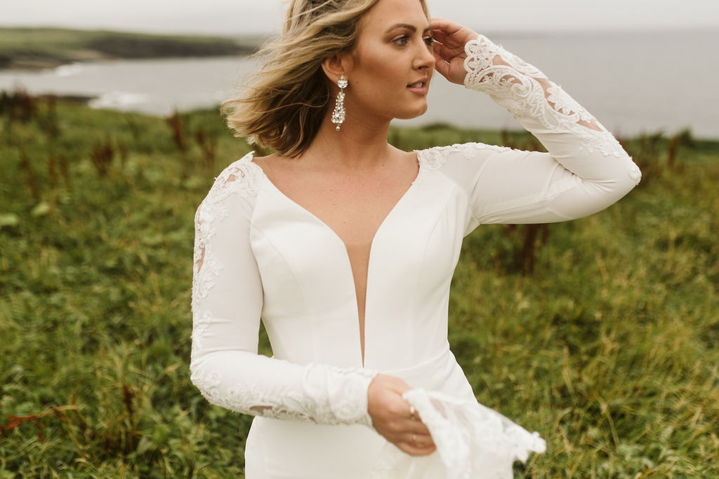 Bride wears a simple fitted wedding dress with plunge neckline and long sleeves with lace detail while looking at the Atlantic Ocean in Mullaghmore Head in Ireland