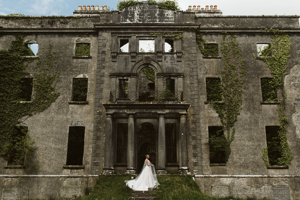 Brides stands on the steps of Moore Hall in Ireland wearing a simple ballgown wedding dress with tulle cape