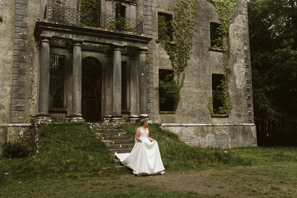 Brides walks down the steps of abandoned Moore Hall in Ireland wearing a simple ballgown wedding dress with tulle cape