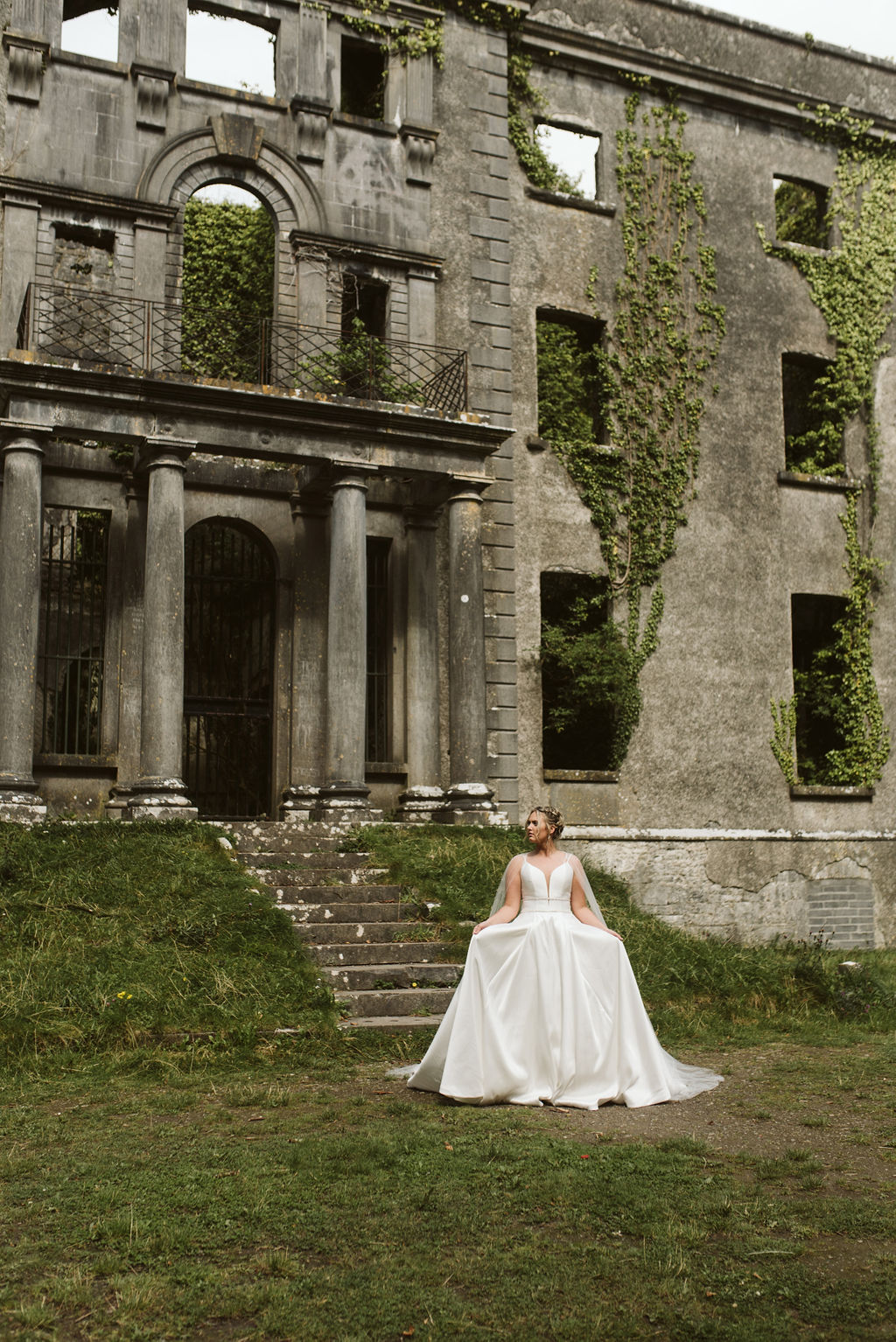 Bride stands in front of abandoned Moore Hall wearing a simple ballgown wedding dress with a plunging neckline in Ireland