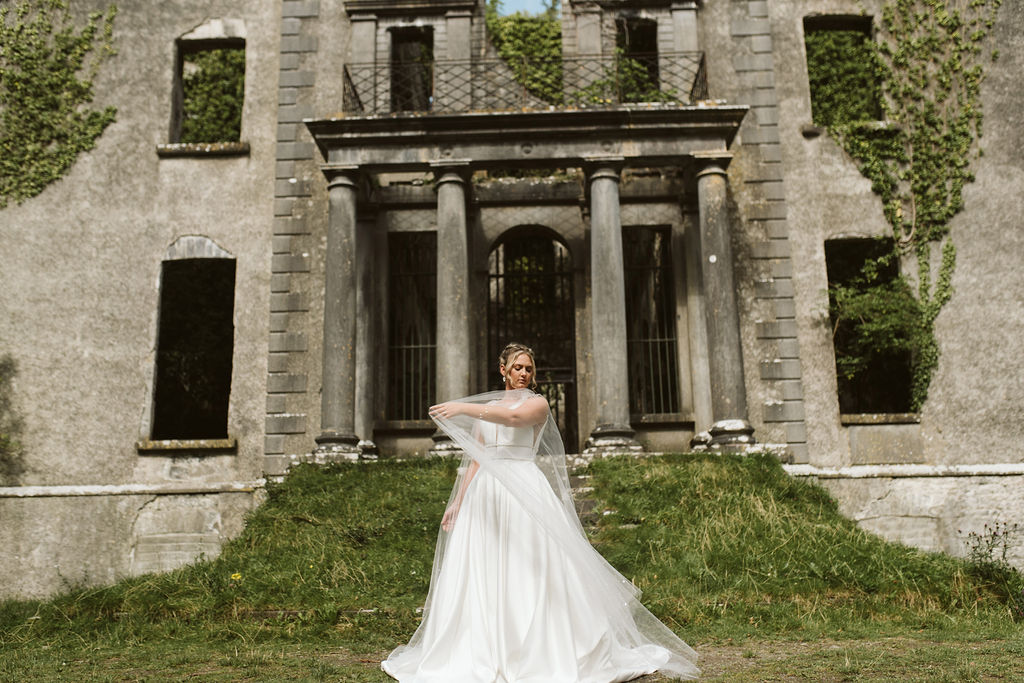 Bride plays with tulle cape wearing a simple ballgown wedding dress at Moore Hall in Ireland