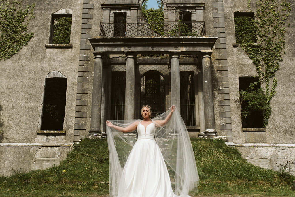 Bride plays with tulle cape in front of Moore Hall in Ireland wearing a simple ballgown wedding dress with plunging neckline