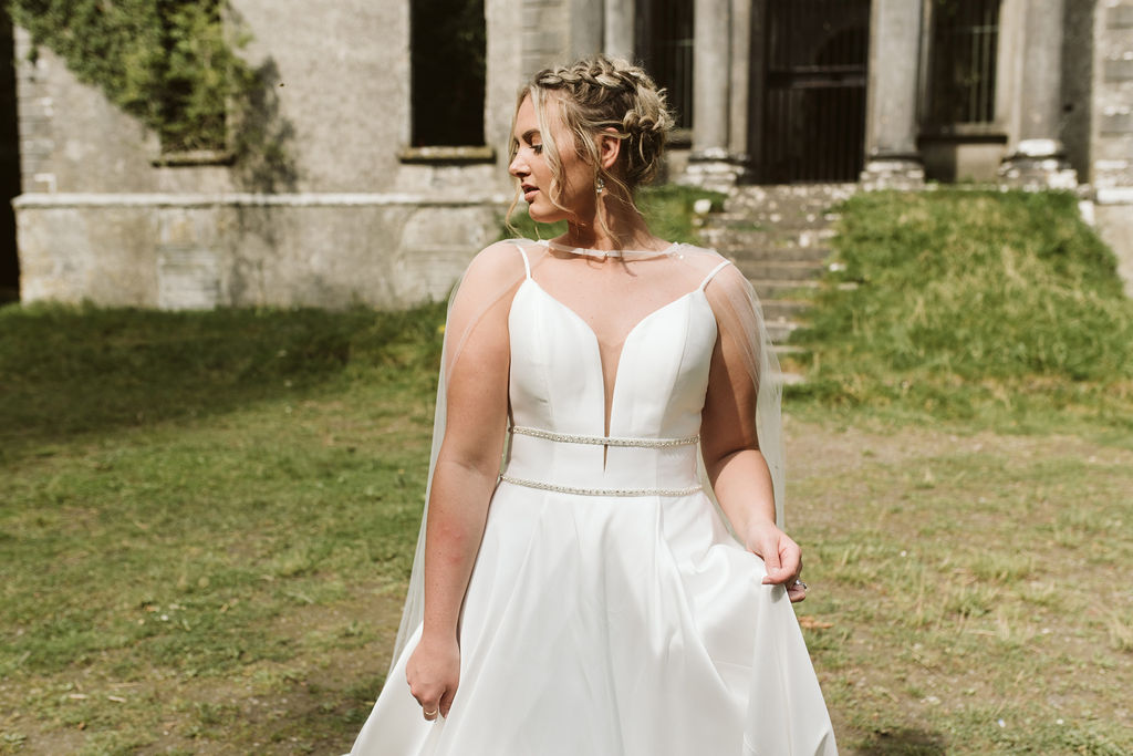 Bride with dutch braids stands in front of Moore Hall in Ireland wearing a simple ballgown wedding dress with plunging neckline, beaded waist detail and tulle bridal cape