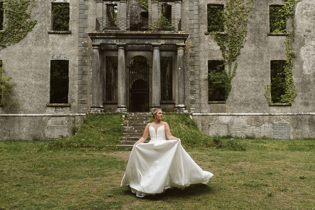 Brides runs on the grounds of Moore Hall in Ireland wearing a simple ballgown wedding dress with plunging neckline and beaded waist detail
