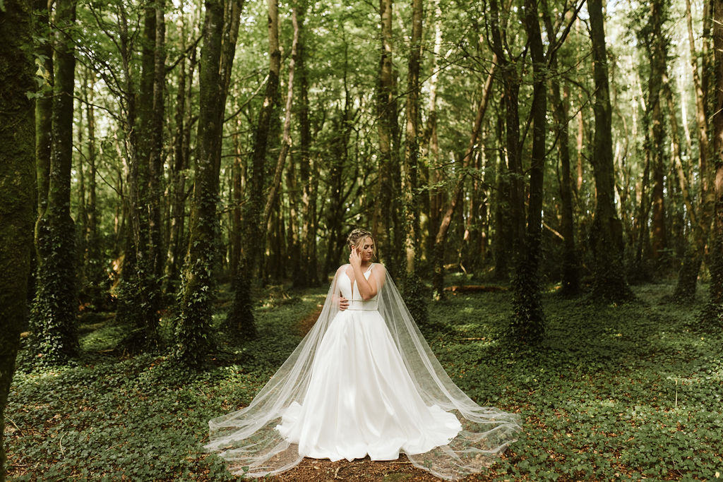 Bride with dutch braids stands in middle of forest wearing a simple ballgown wedding dress with a tulle bridal cape in Ireland