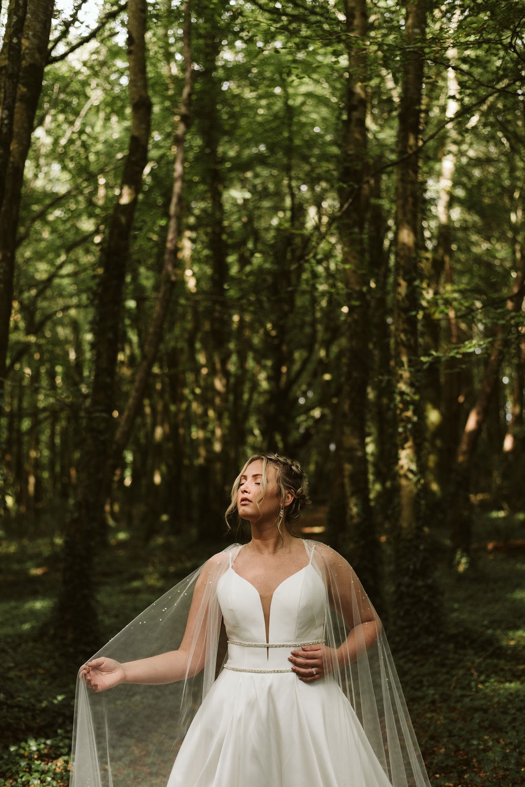 Sun hits bride's face in the middle of the woods in Ireland while she's wearing a simple ballgown wedding dress with beaded waist detail and a tulle bridal cape