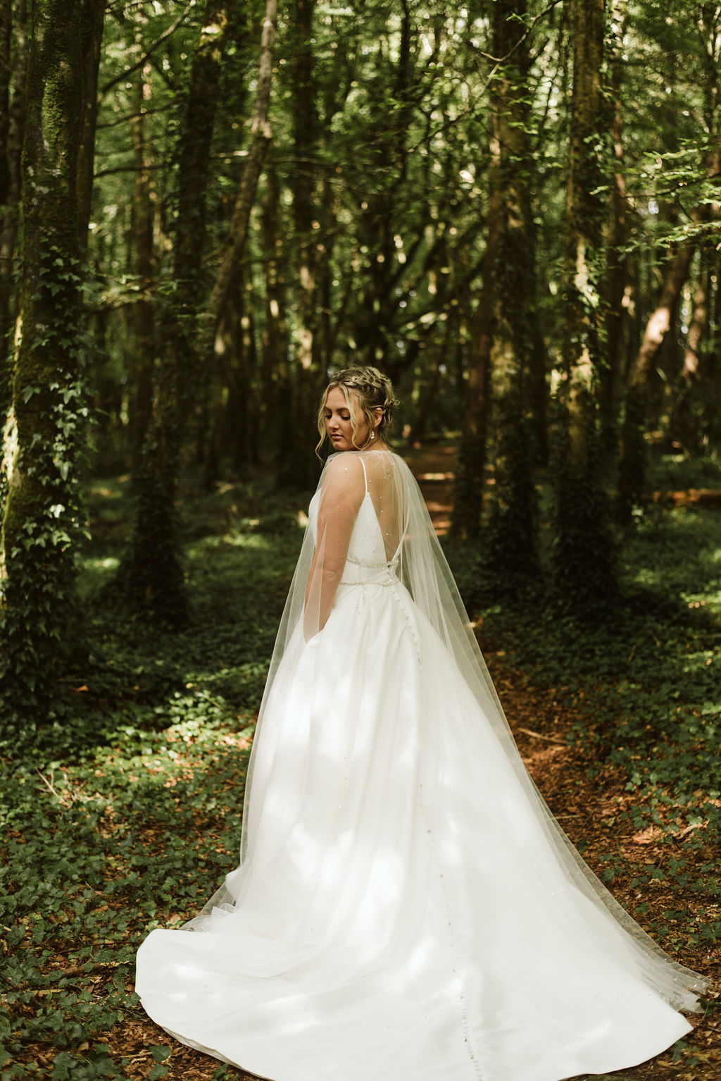 Back view of bride looking over her shoulder on the grounds of Moore Hall in Irealnd wearing a simple ballgown with open back and beaded waist detail and tulle bridal cape