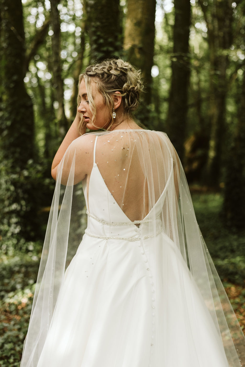 Back view of bride wearing an open back simple ballgown wedding dress with beaded waist detail and tulle bridal cape with braids in her hair