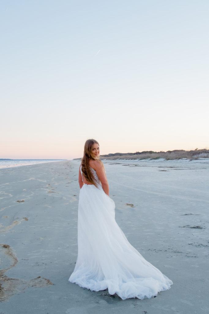 open back wedding dress on beach at sunrise