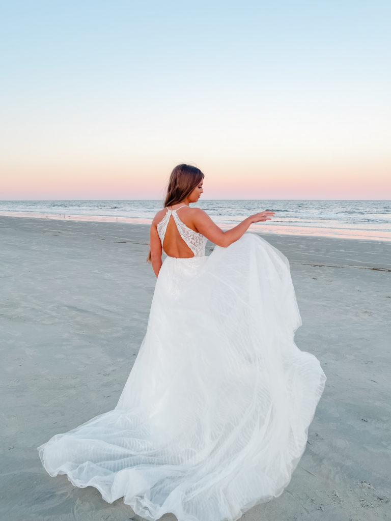 back of beaded lace and tulle aline wedding dress on beach at sunrise