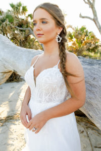 close up of beaded lace and tulle wedding dress at driftwood beach