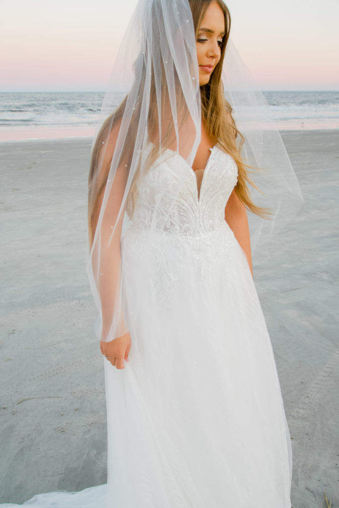lace and tulle aline wedding dress with fingertip length veil on beach at sunrise